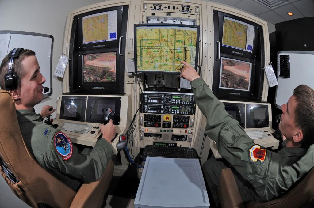 """Un poste de pilotage d'UAV (un Predator en l'occurence) avec ses opérateurs. Chaque UAV peut disposer d'un poste différent mais cela illustre bien la différence avec un cockpit où le pilote peut toujours """"voir"""" l'extérieur. (c) USAF"""
